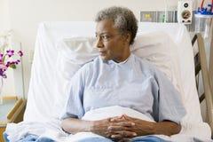 Mujer mayor que se sienta en cama de hospital Fotografía de archivo