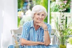 Mujer mayor que se sienta en casa Foto de archivo
