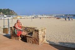 Mujer mayor que se sienta en el banco de piedra y que toma el sunbath en la playa de Blanes Foto de archivo libre de regalías