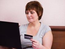 Mujer mayor que se sienta en el dormitorio con la tarjeta del ordenador portátil y de banco Imagenes de archivo