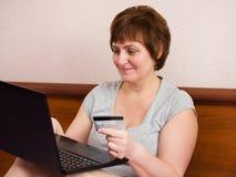 Mujer mayor que se sienta en el dormitorio con la tarjeta del ordenador portátil y de banco Foto de archivo libre de regalías