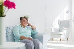 Mujer mayor que se sienta en el sofá imagenes de archivo
