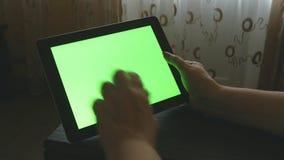 Mujer mayor que se sienta en el sofá en casa y que usa una PC digital de la tableta con la pantalla verde metrajes
