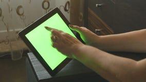 Mujer mayor que se sienta en el sofá en casa y que usa una PC digital de la tableta con la pantalla verde, visión trasera Tablet  almacen de video