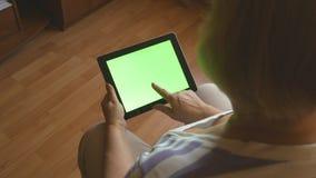 Mujer mayor que se sienta en el sofá en casa y que usa una PC digital de la tableta con la pantalla verde, visión trasera Tablet  metrajes