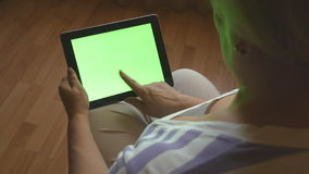 Mujer mayor que se sienta en el sofá en casa y que usa una PC digital de la tableta con la pantalla verde, visión trasera Tablet  almacen de metraje de vídeo