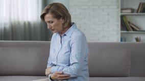 Mujer mayor que se sienta en el sofá, sintiendo problemas presionados, psicológicos, crisis almacen de metraje de vídeo