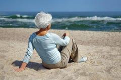 Mujer mayor que se sienta en la arena en el mar de la playa Foto de archivo libre de regalías