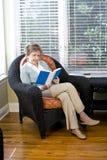 Mujer mayor que se sienta en la lectura de la silla de la sala de estar Imagenes de archivo