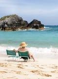 Mujer mayor que se sienta en la playa Foto de archivo libre de regalías