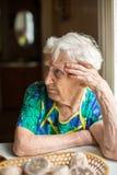 Mujer mayor que se sienta en la tabla Imagenes de archivo