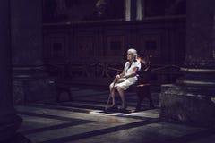 Mujer mayor que se sienta en luz coloreada en banco de iglesia