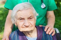 Mujer mayor que se sienta en sillón de ruedas Foto de archivo libre de regalías