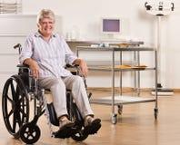Mujer mayor que se sienta en sillón de ruedas Fotos de archivo
