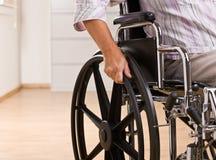 Mujer mayor que se sienta en sillón de ruedas