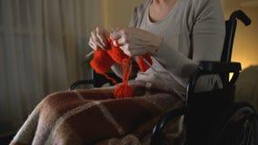 Mujer mayor que se sienta en silla de ruedas y que hace punto, afición agradable, cierre para arriba almacen de video