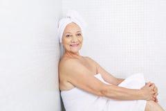 Mujer mayor que se sienta en sitio de la relajación en balneario Foto de archivo libre de regalías