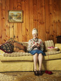 Mujer mayor que se sienta en Sofa Knitting foto de archivo