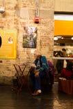 Mujer mayor que se sienta en un papel de las noticias de la lectura de la silla en Chelsea Market en New York City foto de archivo libre de regalías