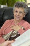 Mujer mayor que se sienta en un sofá y listeting el bookstory imagen de archivo libre de regalías