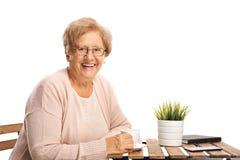 Mujer mayor que se sienta en una mesa de centro y una sonrisa foto de archivo libre de regalías