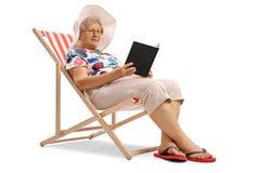Mujer mayor que se sienta en una silla de cubierta y que lee un libro fotos de archivo libres de regalías