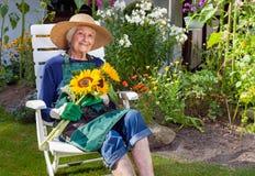 Mujer mayor que se sienta en una silla que sostiene los girasoles foto de archivo libre de regalías