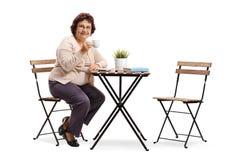 Mujer mayor que se sienta en una tabla del cofee fotos de archivo