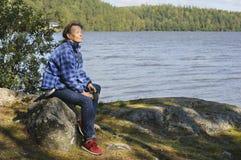 Mujer mayor que se sienta por un lago Foto de archivo
