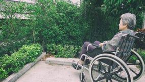 Mujer mayor que se sienta solamente en una silla de ruedas hacia fuera en el jardín Imagenes de archivo