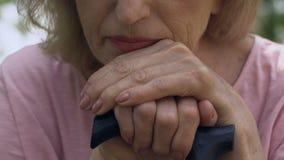 Mujer mayor que se sienta solamente, inclinándose en su bastón y sintiendo ascendente solo, cercano metrajes