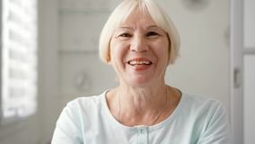 Mujer mayor que sienta en casa hablar vía el mensajero app Skype Mano que agita sonriente en el saludo almacen de video