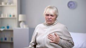 Mujer mayor que siente repentinamente el ataque del corazón, problemas de salud en edad avanzada imagen de archivo