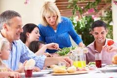 Mujer mayor que sirve una comida de la familia Imagen de archivo libre de regalías