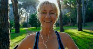 Mujer mayor que sonríe en el parque 4k almacen de video