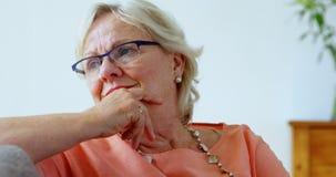 Mujer mayor que sonríe en la sala de estar 4k almacen de metraje de vídeo