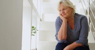 Mujer mayor que sonríe en las escaleras 4k almacen de metraje de vídeo