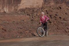Mujer mayor que sonríe en una bici Foto de archivo libre de regalías