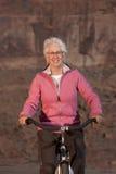 Mujer mayor que sonríe en una bici Imagen de archivo libre de regalías
