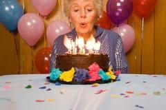 Mujer mayor que sopla hacia fuera velas en la torta Foto de archivo libre de regalías