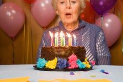 Mujer mayor que sopla hacia fuera velas en la torta Fotos de archivo libres de regalías