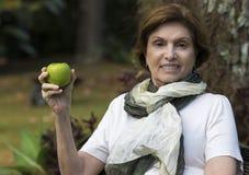 Mujer mayor que sostiene Apple fresco debajo del árbol Fotografía de archivo