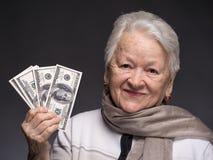 Mujer mayor que sostiene el dinero en manos Fotos de archivo