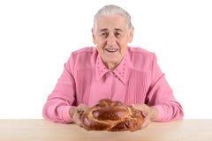 Mujer mayor que sostiene el pan Imágenes de archivo libres de regalías