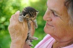 Mujer mayor que sostiene el pequeño gatito Imágenes de archivo libres de regalías