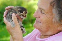 Mujer mayor que sostiene el pequeño gato Fotografía de archivo libre de regalías