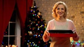 Mujer mayor que sostiene el plato de la Navidad que mira en la cámara, atmósfera del día de fiesta fotos de archivo