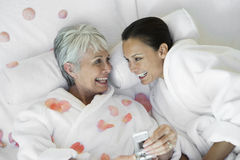 Mujer mayor que sostiene el teléfono móvil mientras que mira a su amigo imagenes de archivo
