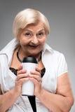 Mujer mayor que sostiene la taza del termo foto de archivo