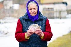 Mujer mayor que sostiene píldoras en su mano Hembra mayor con las píldoras o los meds farmacéuticos Imágenes de archivo libres de regalías